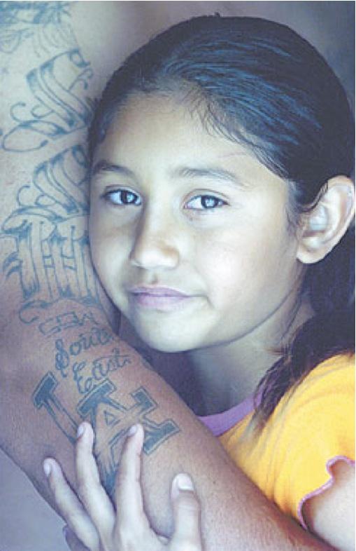 Little Girl In Tattoed Arm Embrace