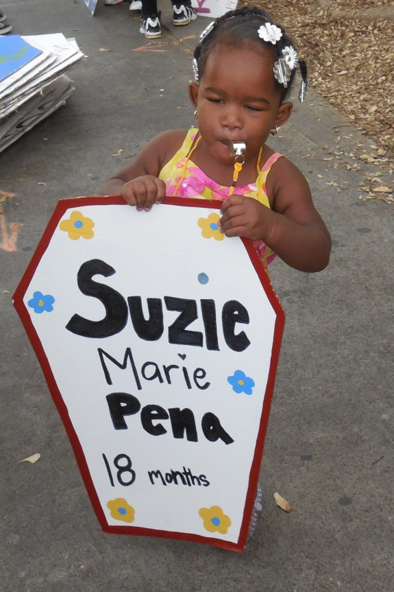 Desire Brown holding the coffin of 18 month old Suzie Marie Pena killed my Law Enforcement.